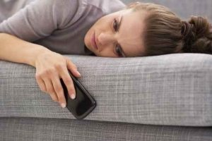 Stressed young woman with cell phone laying on couch